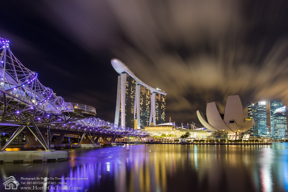 Home On Travel - Singapore skyline of marina bay in Singapore at night with Helix Bridge and Marina Bay Sands Hotel.